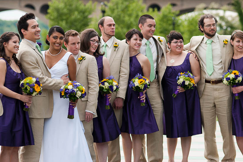 wedding party with linen suits, green ties and purple dresses