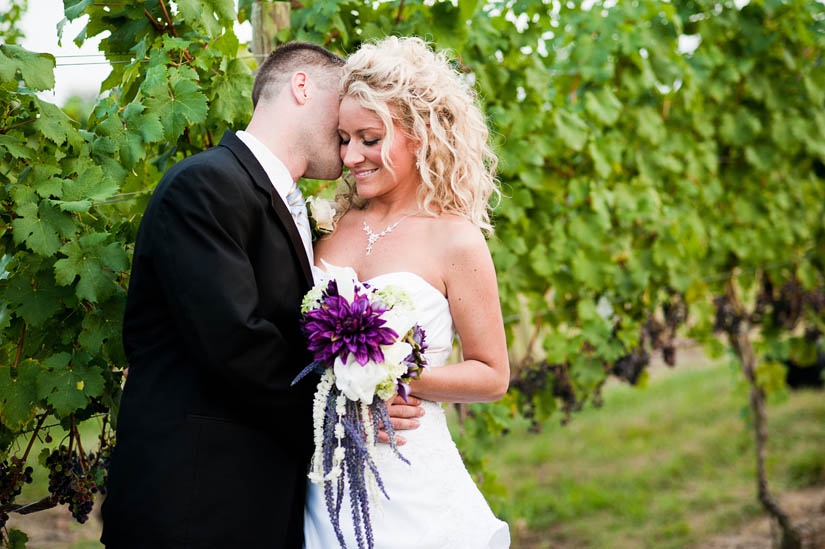 bride and groom in vines at miracle valley vineyard