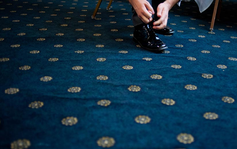 groom ties his shoes on carpet