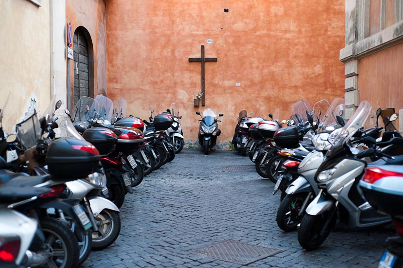 cross and vespas in rome, italy