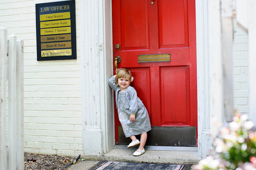 sweet little girl in front of red door in old town alexandria