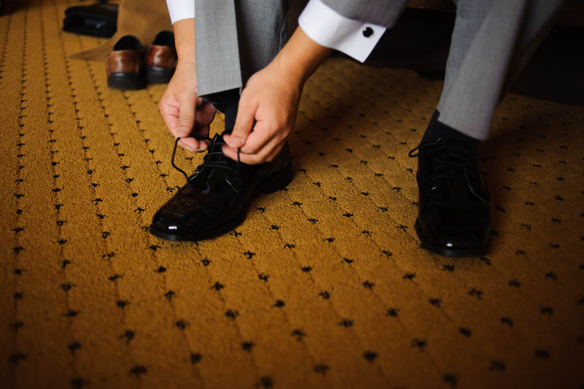 groom tying his shoelaces before his wedding
