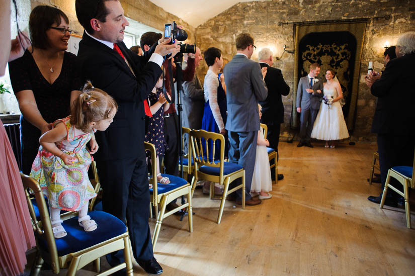 little girl looking at the bride and groom at danby castle wedding