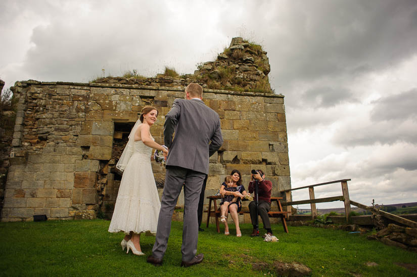 bride and groom in front of castle ruins in north yorkshire