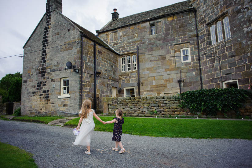 little girls walking hand-in-hand at danby castle wedding