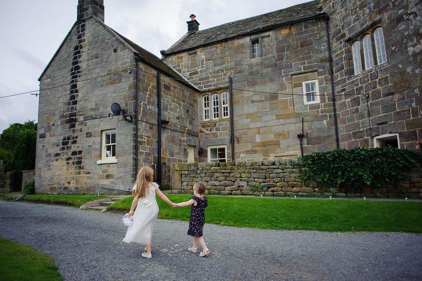 little girls walking hand-in-hand at danby castle wedding