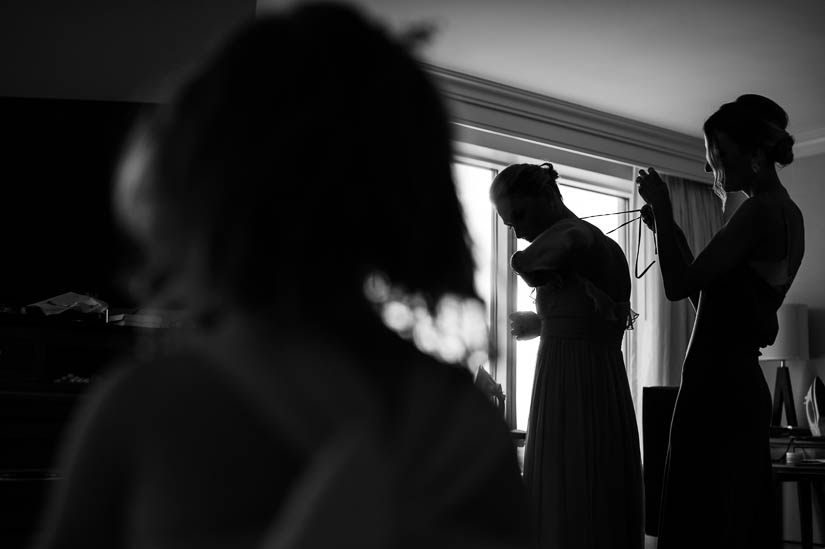 bride helping her sister get dressed before the wedding