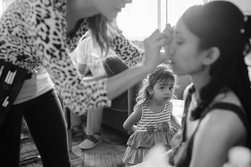 little girl looks on as bride has her makeup done