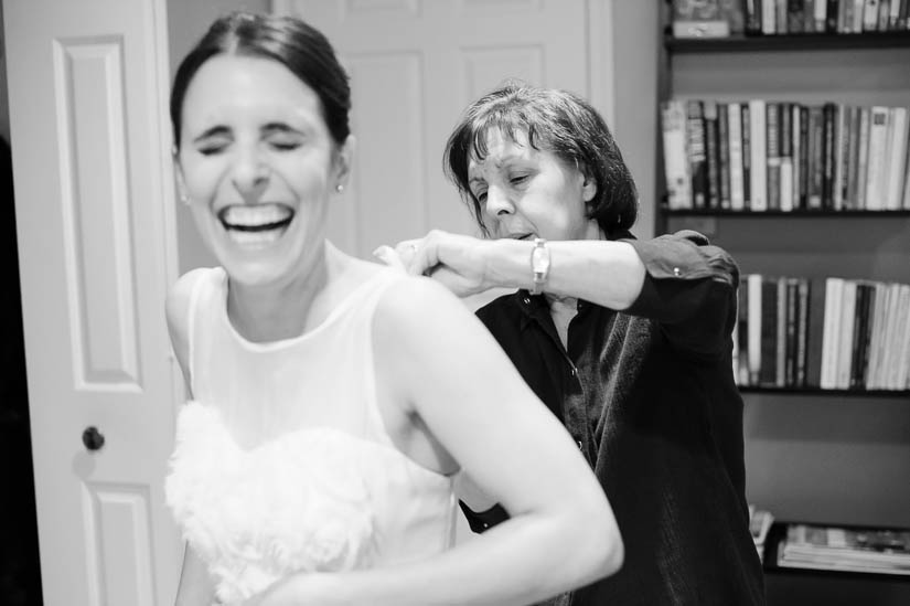 mom helping her daughter dress before the wedding