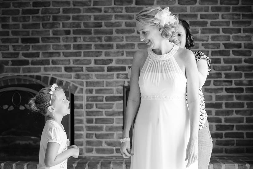 bride and flower girl talking while she puts her dress on